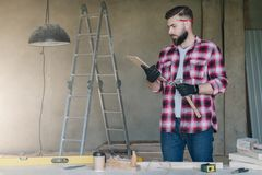 Bearded hipster man is carpenter, builder, designer stands in wo. Rkshop,holds clipboard and hammer, reads instruction.On desk construction tools,in background royalty free stock photography