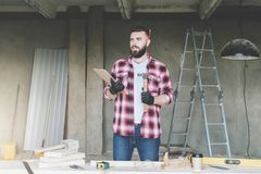 Bearded hipster man is carpenter, builder, designer stands in workshop,holds clipboard and hammer, reads instruction. On desk construction tools,in background royalty free stock image