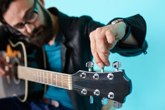 Bearded hipster man hand adjusting on acoustic guitar. stock photos