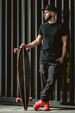 Bearded hipster man holding longboard and posing. Bearded hipster man in black shirt holding longboard and posing on a background of a metal fence. Full body Royalty Free Stock Photography