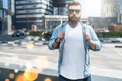 Bearded hipster man in sunglasses dressed in white t-shirt,denim shirt,stands on city street.Mock up.Space for logo,text