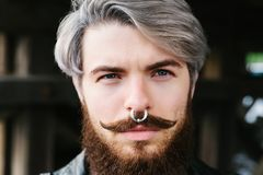 Bearded hipster with nose ring in leather jacket Stock Photo