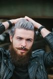 Bearded hipster with nose ring in leather jacket. Outdoor Stock Image