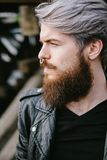 Bearded hipster with nose ring in leather jacket. Outdoor Royalty Free Stock Image