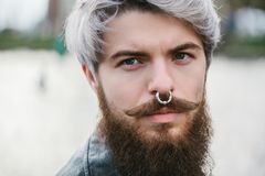 Bearded hipster with nose ring in leather jacket. Outdoor Royalty Free Stock Photography