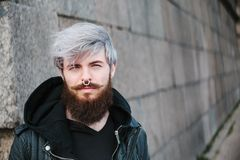 Bearded hipster with nose ring in leather jacket. Outdoor Royalty Free Stock Images