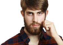 Bearded Hipster. Portrait of handsome bearded young man twisting his mustache on a white background stock image