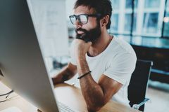 Bearded hipster professional wearing eye glasses working at modern loft studio-office with desktop computer.Panoramic royalty free stock photo