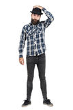 Bearded hipster putting on black fedora hat looking at camera Stock Photography