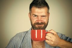 Bearded hipster with red milk cup.