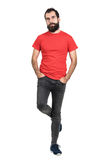 Bearded hipster in red t-shirt standing and balancing on one leg looking away Stock Photo