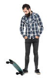 Bearded hipster standing on longboard skate with hands in pocket looking down Royalty Free Stock Photography