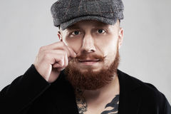 Bearded hipster with tattoo.brutal handsome boy in hat Royalty Free Stock Photos