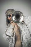Bearded Hipster Trombone. Bearded hipster plays jazz trombone in leopard print bathrobe Royalty Free Stock Image