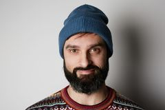 Bearded hipster wearing blue beanie and colored sweater on white background.  royalty free stock images