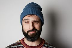 Bearded hipster wearing blue beanie and colored sweater on white background.  royalty free stock photography