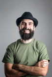 Bearded hipster wearing hat with upper lips piercing friendly laughing at camera. Royalty Free Stock Photo