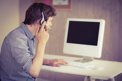 Bearded hipster working at desk with headset Royalty Free Stock Photography
