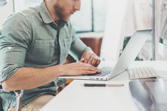 Bearded Hipster Working Table Laptop Modern Interior Design Loft Office.Man Work Coworking Studio,Use contemporary. Notebook,typing keyboard.Blurred Background royalty free stock photos