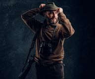 Bearded hunter with rifle and binoculars corrects his hat and looking sideways. Studio photo against a dark wall. Bearded hunter with rifle and binoculars royalty free stock images