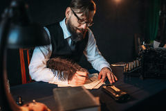 Bearded journalist in glasses writes with feather Royalty Free Stock Photography