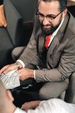 Bearded lawyer behaving illegal while receiving bribe from client royalty free stock photography