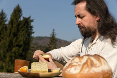 Bearded and long-haired man making a light meal Stock Photos