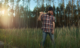 Bearded Lumberjack in Hat holding a big Axe on Shoulder Royalty Free Stock Images