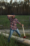 Bearded Lumberjack holding a big Ax in Hand and wipes the Sweat Stock Photos