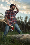 Bearded Lumberjack holding a big Ax in one Hand and wipes the Sw Royalty Free Stock Image