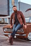 Bearded male dressed in brown leather jacket and boots leaning on tuned retro car in the city parking near skyscraper. Country style concept. Bearded male royalty free stock image