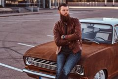 Bearded male dressed in brown leather jacket posing with crossed arms while leaning on tuned retro car in the city stock image