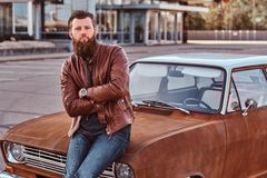 Bearded male dressed in brown leather jacket posing with crossed arms while leaning on tuned retro car in the city stock images