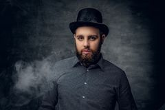Bearded male smoking electronic cigarette over grey background. Bearded male dressed in a grey fleece shirt and tot hat smoking electronic cigarette over grey Royalty Free Stock Photos