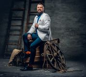 Bearded male dressed in a jeans, white jacket and bow tie sits o. N a wooden box with ladder and a wooden wheel on a background Stock Photo