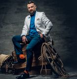 Bearded male dressed in a jeans, white jacket and bow tie sits o. N a wooden box with ladder and a wooden wheel on a background Stock Photography
