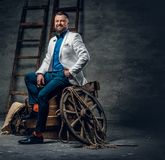 Bearded male dressed in a jeans, white jacket and bow tie sits o. N a wooden box with ladder and a wooden wheel on a background Stock Image