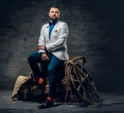 Bearded male dressed in a jeans, white jacket and bow tie sits o. N a wooden box with ladder and a wooden wheel on a background Royalty Free Stock Image