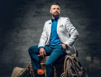 Bearded male dressed in a jeans, white jacket and bow tie sits o. N a wooden box with ladder and a wooden wheel on a background Royalty Free Stock Photos