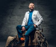 Bearded male dressed in a jeans, white jacket and bow tie sits o. N a wooden box with ladder and a wooden wheel on a background Royalty Free Stock Photography