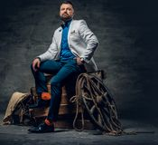 Bearded male dressed in a jeans, white jacket and bow tie sits o. N a wooden box with ladder and a wooden wheel on a background Royalty Free Stock Images