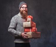 Bearded male holds Christmas gifts. royalty free stock image
