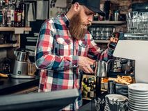 Positive bearded male at the counter using cash register in a coffee shop. Bearded male is making coffee in a coffee shop Royalty Free Stock Photo