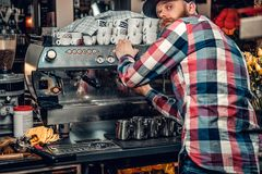 A man is making coffee in a professional coffee machine. Bearded male is making coffee in a professional coffee machine Stock Images