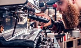 A man is making coffee in a professional coffee machine. Bearded male is making coffee in a professional coffee machine Stock Photography