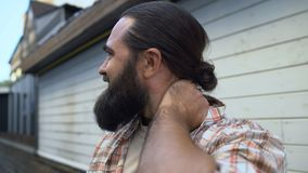 Bearded male massaging neck to relieve pain, muscle spasm, osteochondrosis