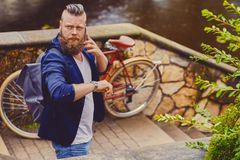 Bearded male in a park talks by smart phone. Casual bearded male in a park talks by smart phone stock image