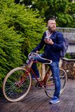 Bearded male in a park talks by smart phone. stock images