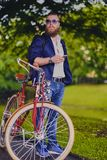 Bearded male in a park talks by smart phone. Casual bearded male in a park talks by smart phone royalty free stock photography