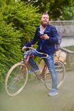 Bearded male in a park talks by smart phone. royalty free stock images